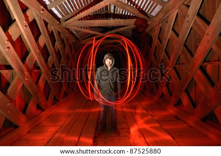sinister guy surrounded by red light in a spooky tunnel