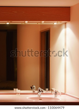 Sink and mirror in bathroom of hotel - stock photo