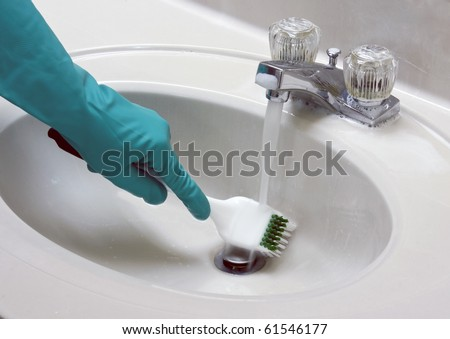 sink cleaned with a gloved hand and brush - stock photo