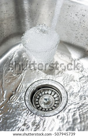 Sink with water and glass