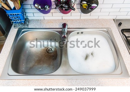 sink with water and white foam - stock photo