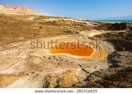 Sinkhole or open pit with orange salty water on the shore's of the dead sea at the end of the summer when the water level is at it's lowest - stock photo