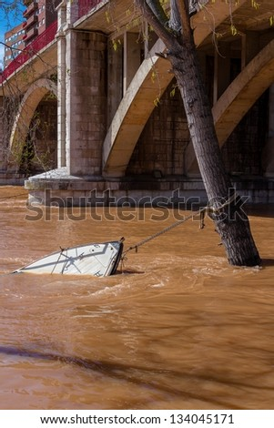 Sinking boat due to the flood in Pisuerga river. - stock photo