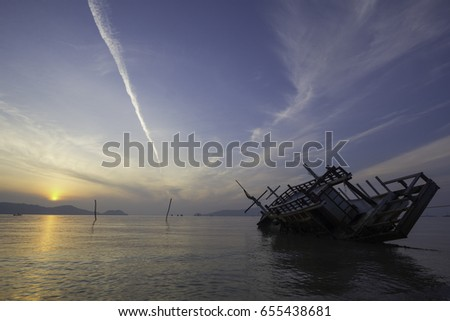 Sinking boat in the sea, view at sunrise