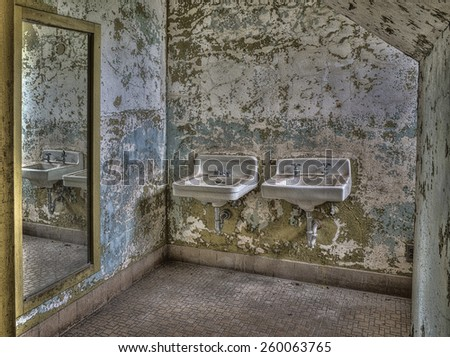 Sinks Reflected in Mirror at Abandoned Pennhurst Asylum in Pennsylvania - stock photo