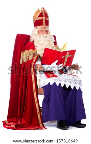 Sinterklaas is resting on his chair, reading in his book - stock photo