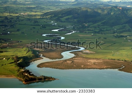 Sinuous river going into the sea - stock photo