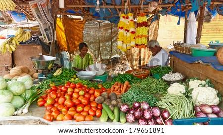 SIOLIM, GOA, INDIA - CIRCA DECEMBER 2013: Elderly couple sells vegetables. - stock photo