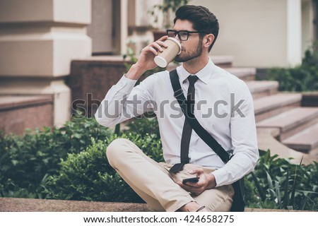 Sip of fresh coffee before working day. Confident young man in glasses drinking coffee and holding his smart phone while sitting outdoors  - stock photo