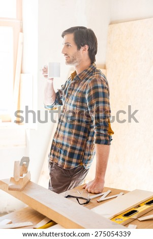 Sip of imagination. Side view of thoughtful young male carpenter holding coffee cup while leaning at the wooden table with diverse working tools laying on it