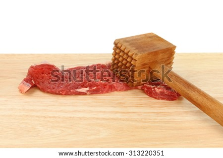 Sirloin steak with a meat mallet on a wooden board against a white background - stock photo