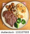 Sirloin steak with dauphinois potatoes, broccoli and mushrooms. - stock photo