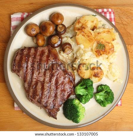 Sirloin steak with dauphinois potatoes, broccoli and mushrooms. - stock photo