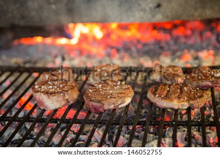 Sirloin steaks on grill and fire, shallow depth of field - stock photo