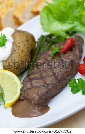 sirloin strip steak with vegetables and savory sauce - stock photo