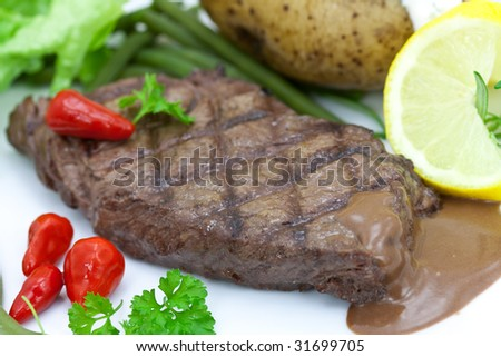 sirloin strip steak with vegetables and savory sauce