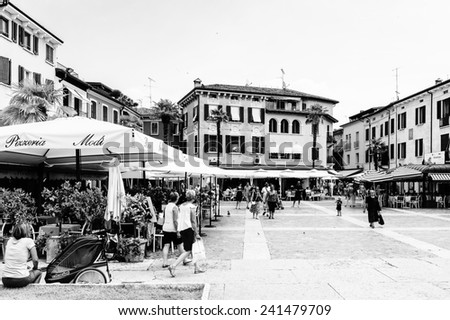 SIRMIONE, ITALY - JUNE 26, 2014: Street restaurant in the Sirmione town, Italy. Sirmione became popular touristic destination on the Lake garda, the largest lake in Italy - stock photo