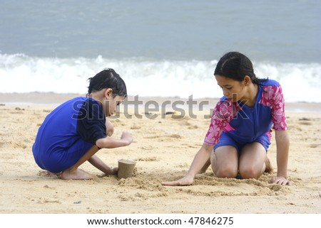 Sister and brother at a tropical beach enjoying the sand together. - stock photo