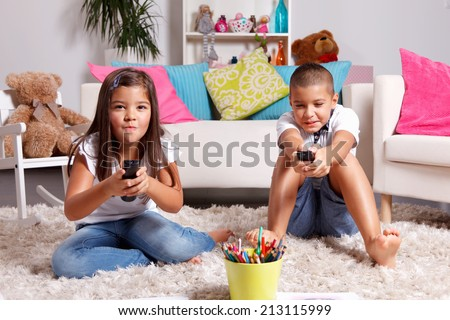 Sister and brother compete for watching TV - stock photo