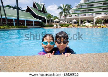 Sister and brother enjoying the resort hotel swimming pool in the tropics - stock photo