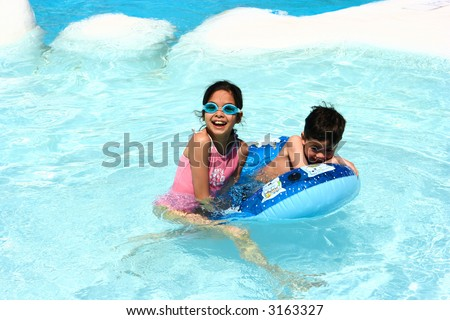 Sister and brother having fun in the swimming pool. - stock photo