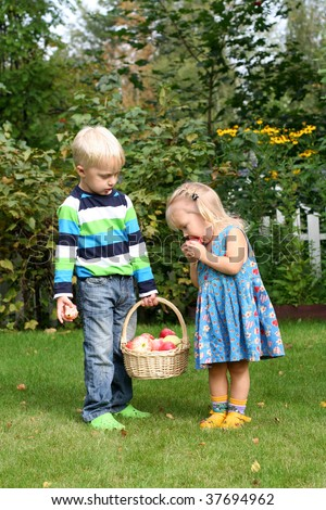 Sister and brother in the apple garden - stock photo