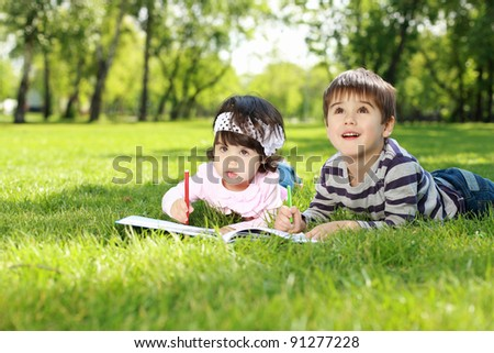 Sister and brother in the park reading a book - stock photo