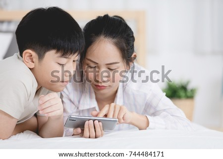 Sister and brother looking into the phone on bed with smiling face .