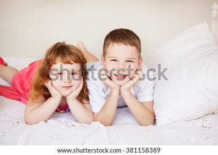 sister and brother lying on the bed