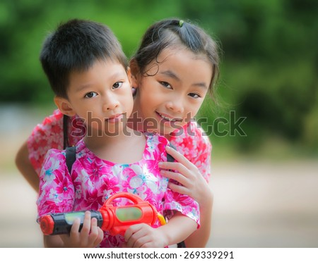 Sister and Brother play water gun in Songkran festival in Thailand - stock photo