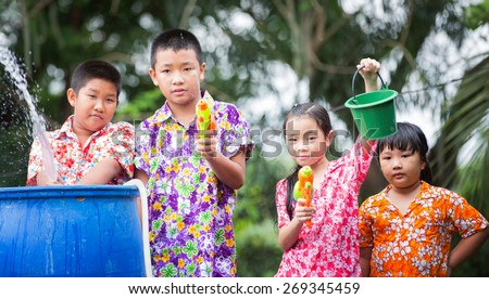 Sister and Brother play water gun in Songkran festival (New year) in Thailand - stock photo