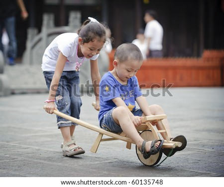 sister and brother play wood trolley