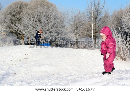 Sister and brother playing in the winter park - stock photo