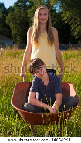 Sister and brother playing outdoors. Shallow DOF, focus on boy's face. - stock photo