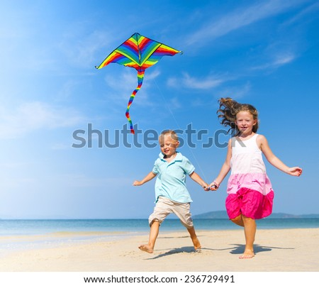 Sister and brother playing with kite on beach. - stock photo