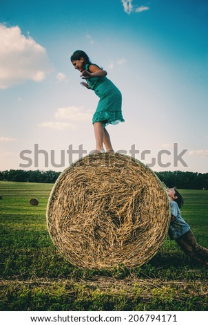 sister and brother playing with wheat dried bale  - stock photo