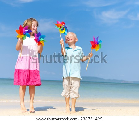 Sister and brother playing with windmill on beach. - stock photo