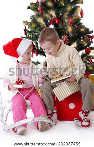 Sister and brother showing Christmas presents to each other - stock photo