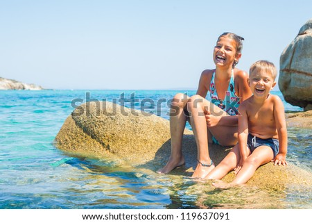 Sister and brother sitting on the stone n the transparent sea - stock photo