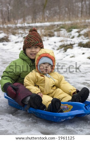 sister and brother tobogganing in a cold winter day - stock photo