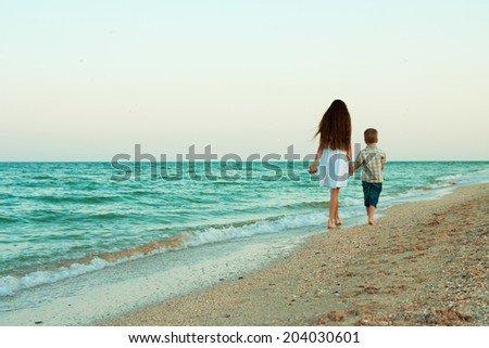 Sister and brother walking away by the evening beach. - stock photo
