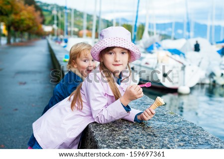 Sister and little brother outdoors in city on a nice autumn day - stock photo