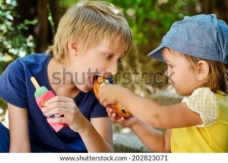 sister feeding her brother outdoors - stock photo