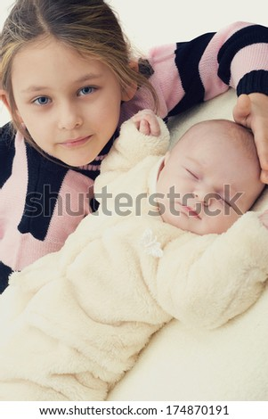 sister gently hugs a newborn - stock photo