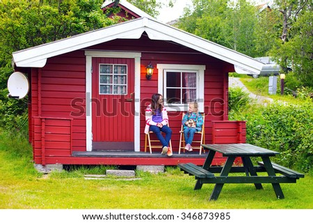 sister girls sitting near the red house at the campsite, Norway  - stock photo