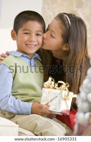 Sister Giving Her Brother A Christmas Present And Kissing Him On The Cheek - stock photo