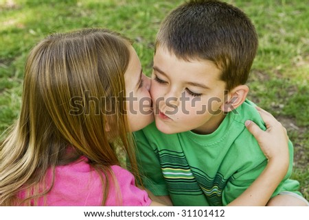 Sister giving her brother a kiss on the cheek - stock photo