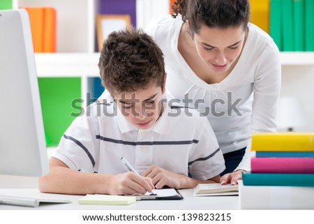 Sister helping brother with homework - stock photo