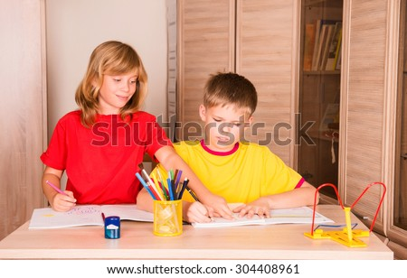 Sister helping her brother with home assignment. Portrait of two cute children working on their homework together. Boy and girl doing homework at home.  - stock photo