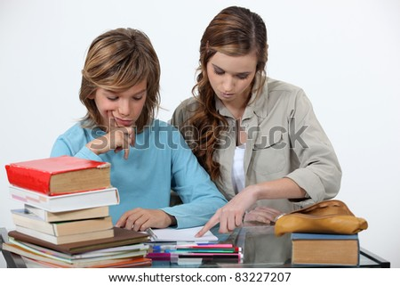 Sister helping her sibling with an assignment - stock photo